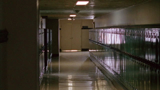 vídeos de stock, filmes e b-roll de wide angle of high or middle school hallway with lockers lining hall. pov moves slightly, could be pov of person waiting in darkened hallway. - colégio educação