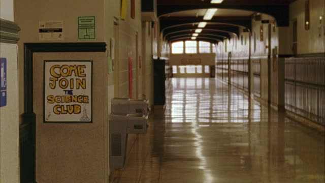 "wide angle of high school or middle school hallway with lockers and drinking fountains. poster on wall reads ""come join the science club."" - junior high stock videos & royalty-free footage"