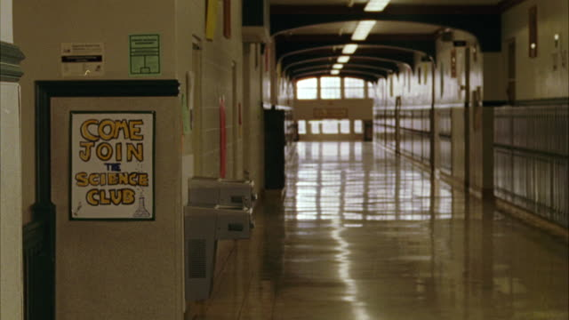 "wide angle of high school or middle school hallway with lockers and drinking fountains. poster on wall reads ""come join the science club."" - 廊下点の映像素材/bロール"