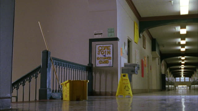 "wide angle of high school or middle school hallway landing with bucket, mop and wet floor poster on floor. sign reading ""come join the science club"" seen on wall. cleaning. - 廊下点の映像素材/bロール"