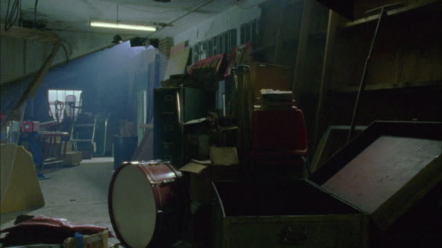 wide angle of cluttered attic in house or school. opened steamer trunk, musical instruments, chairs and other dusty junk seen. - 屋根裏部屋点の映像素材/bロール