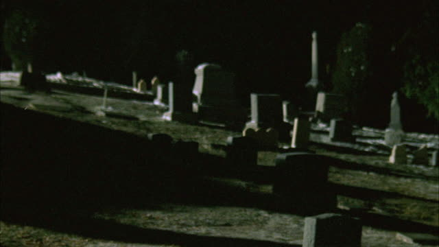 WIDE ANGLE OF CEMETERY WITH TREES, HEADSTONES, TOMBSTONES ON HILLSIDE. LIGHT SPRINKLING OF SNOW SEEN. FOOTAGE IS SCRATCHED AND BLURRY IN PARTS.