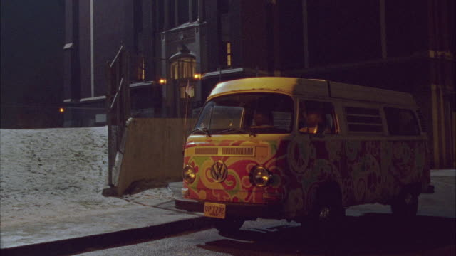 wide angle of volkswagen bus vehicle parked by building. snow on ground. - bus stock-videos und b-roll-filmmaterial