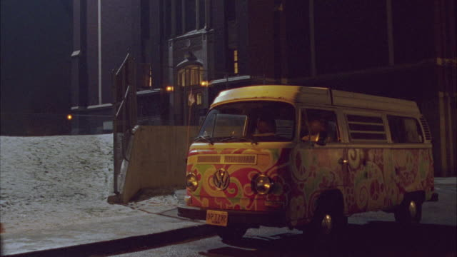 WIDE ANGLE OF VOLKSWAGEN BUS VEHICLE PARKED BY BUILDING. SNOW ON GROUND.