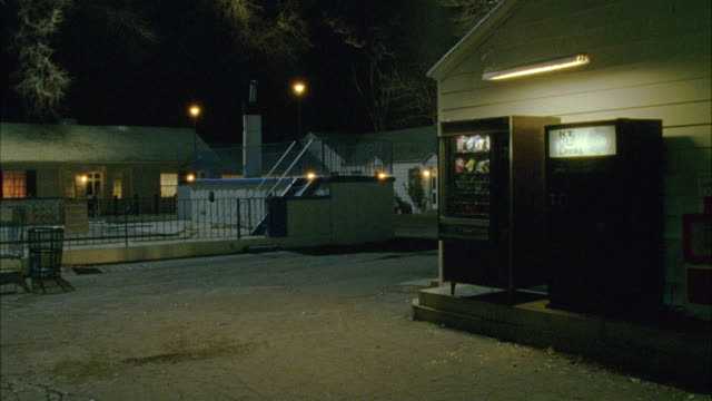 WIDE ANGLE OF VENDING MACHINES OUTSIDE MOTEL. FENCED IN POOL AND MANAGER'S CABIN SEEN IN BACKGROUND.