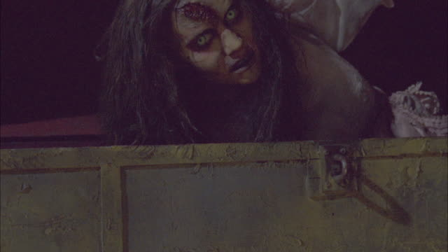 medium angle of metal box opening and dead zombie woman with green eyes, a pink dress and a bloody hole in head crawling out. blinking strobe light flashes. gore - zombie stock videos & royalty-free footage