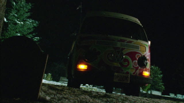 WIDE ANGLE OF MULTI-COLORED VOLKSWAGEN HIPPIE BUS PARKED IN SNOWY GRAVEYARD OR CEMETERY. PARKING LIGHT TURN ON AND EMERGENCY FLASHERS OR HEADLIGHTS FLASH. SEE HEADSTONE OR GRAVESTONE IN FOREGROUND.