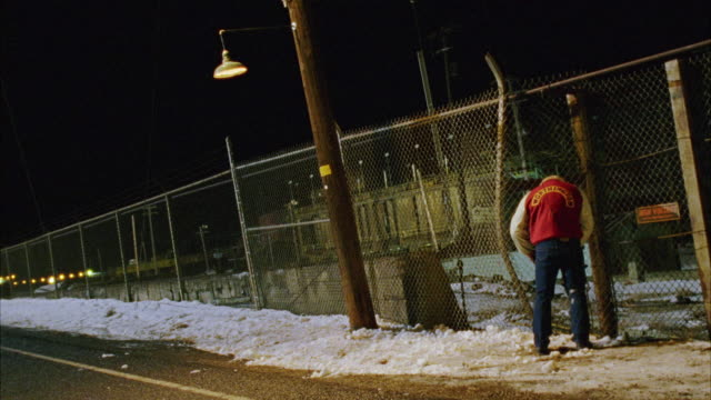 wide angle of man or student in varsity jacket urinating on a chain link electric fence near light pole. see sparks and explosion when man gets electrocuted and falls backward. could be prank. see snow on ground. see stunt wire. - varsity jacket video stock e b–roll