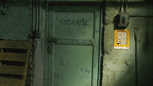 medium angle moving toward storage room door in basement or warehouse. see chain dangling in foreground near concrete walls. door shaking. could be someone trapped. - door chain stock videos & royalty-free footage