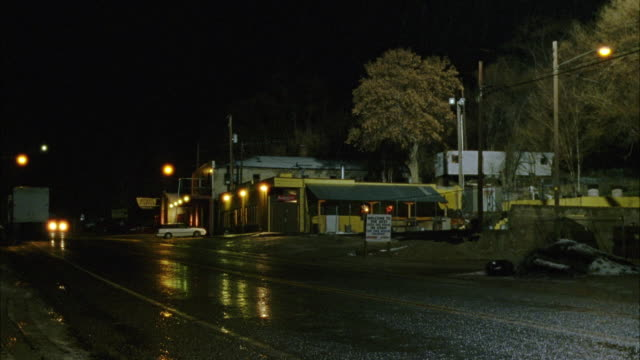 WIDE ANGLE OF SMALL TOWN STREET. PICKUP TRUCK DRIVES BY LEFT TO RIGHT. STREETS ARE WET FROM RAIN. LAMP POSTS IN BACKGROUND.