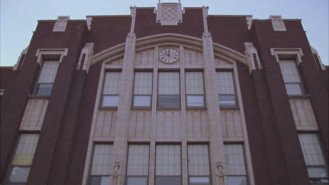 stockvideo's en b-roll-footage met pan down from rooftop of brick high school building to show entry way, front doors with police, security guards posted in front. three story school has clock, marble accents. - bewakingspersoneel