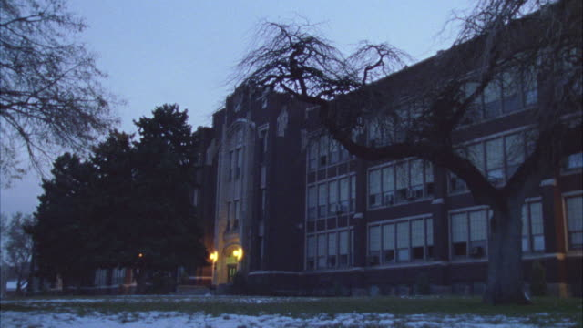 WIDE ANGLE OF THREE STORY BRICK HIGH SCHOOL BUILDING.  SNOW SEEN ON GROUND IN FRONT OF DARKENED SCHOOL. COULD BE USED FOR DUSK.