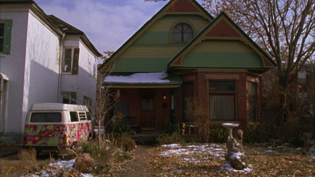steadicam moves through overgrown front yard towards two story lower middle class brick house with victorian details. clip ends on cluttered porch showing front door. colorfully painted volkswagen bus, van parked in driveway next to house. lawn has snow. - brick house stock videos and b-roll footage