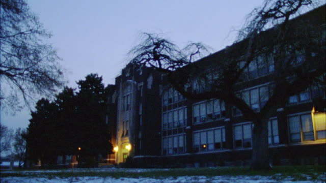 WIDE ANGLE OF THREE STORY BRICK HIGH SCHOOL BUILDING.  SNOW SEEN ON GROUND IN FRONT OF DARKENED SCHOOL. ZOOMS IN ON ENTRY WAY, FRONT DOORS. COULD BE USED FOR DUSK.