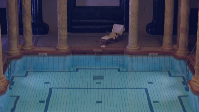 high angle down of swimming pool in hotel or spa. chair with towel visible. pillars and columns. upper class. - budapest video stock e b–roll