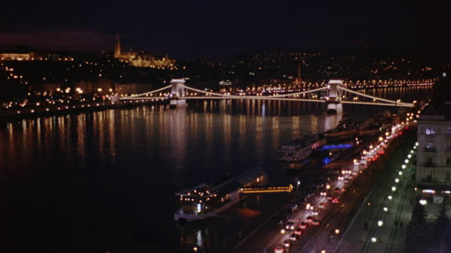 wide angle of chain bridge spanning danube river. cars visible driving on waterfront freeway or highway. barge, ship, boat, or ferry visible in fg. cities. matthias church visible in bg. - ドナウ川点の映像素材/bロール