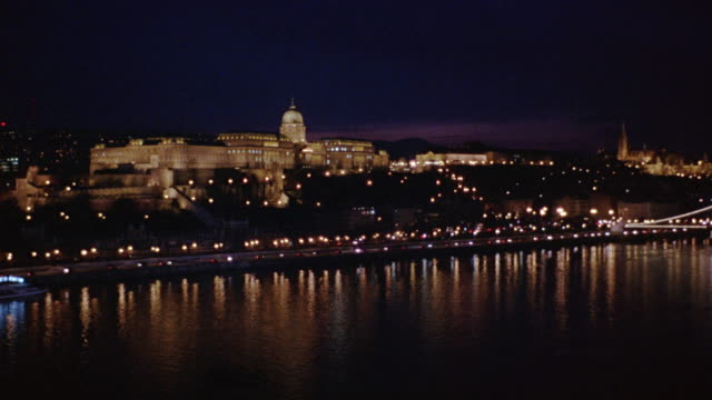 pan left to right and back again from buda castle to wide angle of chain bridge spanning danube river. cars visible driving on waterfront freeway or highway. barge, ship, boat, or ferry visible in fg. cities. matthias church visible in bg. - royal palace of buda stock videos & royalty-free footage