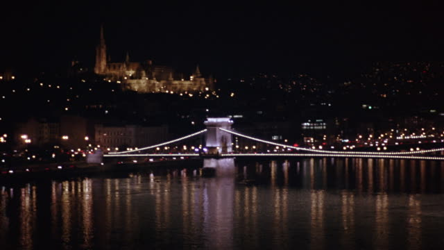 pan left to right and back again from buda castle to wide angle of chain bridge spanning danube river. cars visible driving on waterfront freeway or highway. barge, ship, boat, or ferry visible in fg. cities. matthias church visible in bg. - river danube stock videos & royalty-free footage