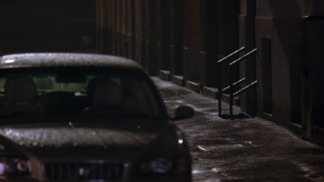 medium angle of sidewalk on dark street. could be alley. car parked at curb in fg. street, car, and sidewalk wet with rain. entrance visible off sidewalk with metal railings. - alley stock videos & royalty-free footage