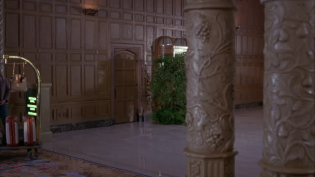 wide angle of upper class hotel lobby. bellhop pushes luggage cart for two hotel guests, a man and woman. couple. marble floors. ornate wood walls. carvings on wooden posts in fg. - gast stock-videos und b-roll-filmmaterial