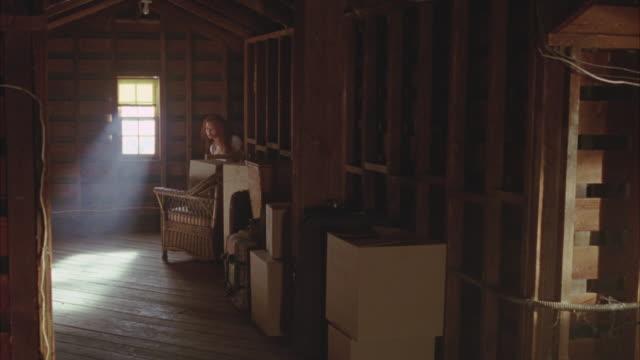 wide angle of attic. bare wooden walls and floor. cardboard boxes stacked against wall. sunlight coming through window. storage. - vindsvåning bildbanksvideor och videomaterial från bakom kulisserna