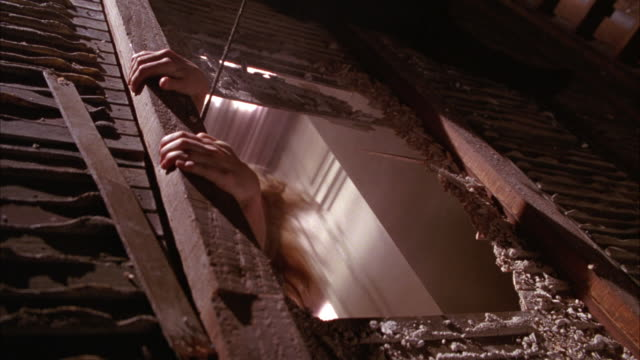 close angle of woman falling through attic floor and hanging, dangling from ceiling above room below. desperately trying not to fall. wood and plaster dust. bare feet and legs. stunt. - loft stock videos and b-roll footage