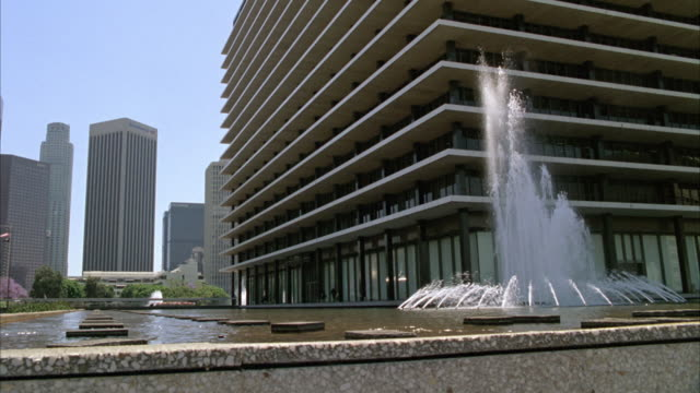 wide angle of fountain outside los angeles department of water and power building. stepping stone or rocks in fountain. blue sky and los angeles city skyline in bg. - stepping stone stock videos & royalty-free footage