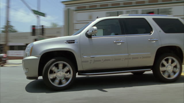 medium angle tracking shot of 2009 cadillac escalade hybrid driving on suburban street or road. suv turns into neighborhood. - sports utility vehicle stock-videos und b-roll-filmmaterial