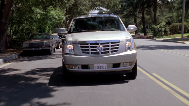 stockvideo's en b-roll-footage met medium angle tracking shot of 2009 cadillac escalade hybrid suv driving on suburban street or road. other vehicles on road and parked at curb.  actual location is altadena, california. - sports utility vehicle