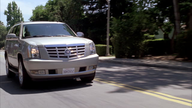 medium angle tracking shot of 2009 cadillac escalade hybrid suv driving on suburban street or road. other vehicles on road and parked at curb. suv drives past houses and trees. could be neighborhood street. actual location is altadena, california. - sports utility vehicle stock-videos und b-roll-filmmaterial
