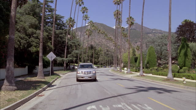 stockvideo's en b-roll-footage met pull back from blue sky, clouds, and mountains to 2009 cadillac escalade hybrid driving on street. upper class suburban neighborhood with palm tree lined streets. mansions. suv makes a u-turn. hedges or shrubs decorate front yards. fire hydrants, mail box - sports utility vehicle