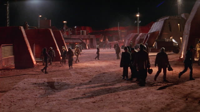 wide angle of workers passing through courtyard of mining camp, military base, or scientific base. workers pass in groups wearing helmets and jumpsuits. small mining truck passes in bg. crowd scatters, showing empty camp. futuristic, small red buildings l - military base stock videos & royalty-free footage