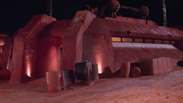 wide angle of adobe-like building at military base, or base for science expedition. interior lights flicker on and off through horizontal window. building and soil in foreground are red. water hose coiled in foreground. could be mining town. science ficti - military base stock videos & royalty-free footage