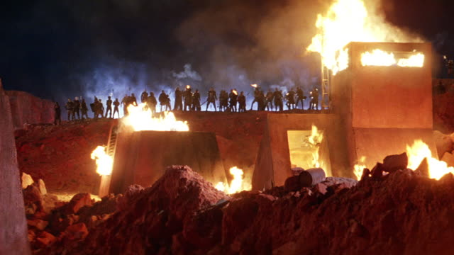 wide angle of warriors or soldiers standing behind building on fire. soldiers stand on hill behind building holding and lighting torches, then raise arms as if to attack. they then run down hill. building is two-story with look-out tower. adobe-style. red - military base stock videos & royalty-free footage