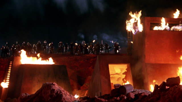 WIDE ANGLE OF WARRIORS OR SOLDIERS STANDING BEHIND BUILDING ON FIRE. SOLDIERS STAND ON HILL BEHIND BUILDING HOLDING AND LIGHTING TORCHES, THEN RAISE ARMS AS IF TO ATTACK. THEY THEN RUN DOWN HILL. BUILDING IS TWO-STORY WITH LOOK-OUT TOWER. ADOBE-STYLE. RED