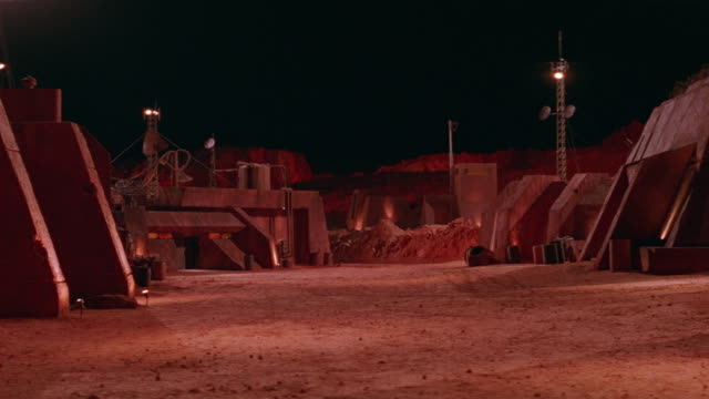wide angle of mining town, military base or similar. pod-like buildings on both sides of dirt courtyard area. cliffs and mine visible in bg. antennas and spotlights above buildings. - military base stock videos & royalty-free footage