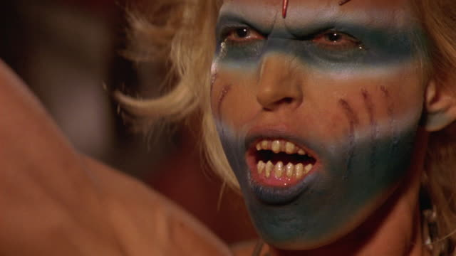 CLOSE ANGLE OF ALIEN ZOMBIE'S FACE AS SHE CHANTS AND RAISES HER HANDS IN THE AIR. CHANT IS WAR CRY OF SOME KIND. MAKE-UP ON FACE. FAKE TEETH.