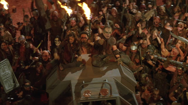 wide angle of angry gang or mob of zombies attacking a military building or fort or prison or industrial building and pulling a military vehicle. torches.  weapons could be sticks or spears. tank. - mob stock-videos und b-roll-filmmaterial
