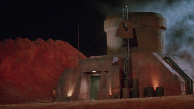 wide angle of futuristic industrial or military building next to red rock  mountain landscape. could be used as a bunker or power plant or factory. smoke in bg. - base militare video stock e b–roll