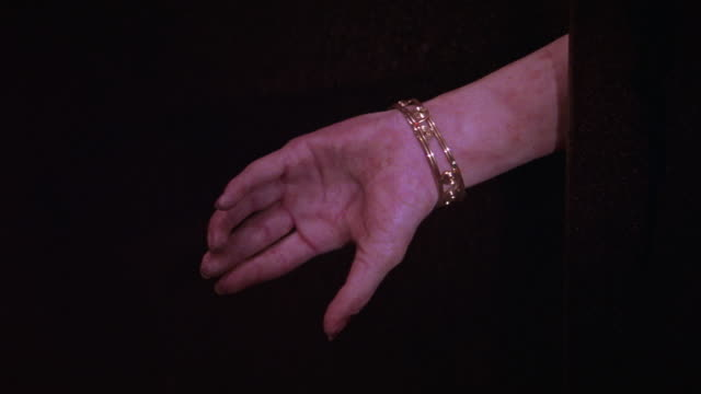 close angle of arm of woman wearing gold bracelet or jewelry. light or flashlight shines on arm. it falls to the floor, severed. blood. human body. gore. could be used for crime scene. - human arm stock videos & royalty-free footage