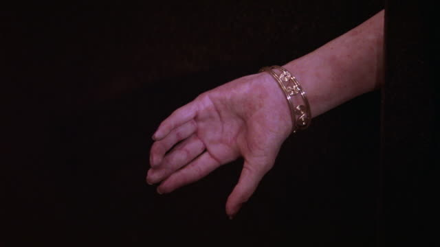 close angle of arm of woman wearing gold bracelet or jewelry. light or flashlight shines on arm and it falls to the floor, severed. blood. human body. gore. could be used for crime scene. - human arm stock videos & royalty-free footage