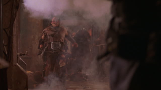 wide angle of warriors or zombies with weapons running through explosion in corridor. ropes, crates, wires in bg. smoke. - モンスター点の映像素材/bロール