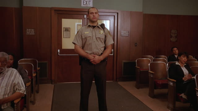 wide angle of man wearing sheriff or police officer uniform standing in center aisle of courtroom. begins to walk forward into foreground. - court room stock videos & royalty-free footage