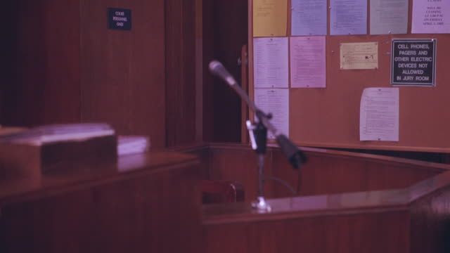 medium angle of witness stand with microphone in courtroom. bulletin board. - witness stock videos & royalty-free footage