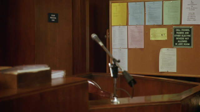medium angle of witness stand with microphone in courtroom. bulletin board. - court room stock videos & royalty-free footage