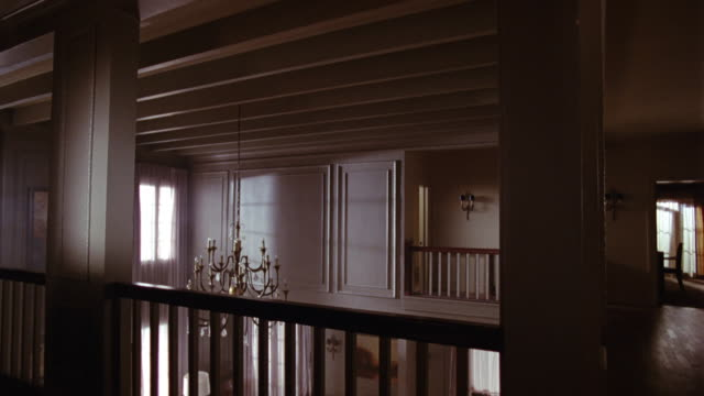 vídeos de stock, filmes e b-roll de wide angle of foyer of house. see ceiling breaking and debris falling and woman falling through wooden floorboards from above. hangs on, swinging by one hand from broken ceiling. woman wears football jersey and has bare legs. see chandelier. stunts. - mansão
