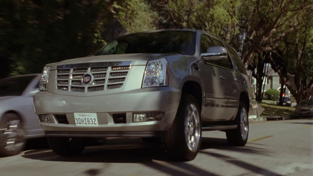 stockvideo's en b-roll-footage met tracking shot of suburban street. ford escalade suv driving down street. passes by houses and residences as we follow. small town setting with trees and foliage lining streets. palm trees. - sports utility vehicle