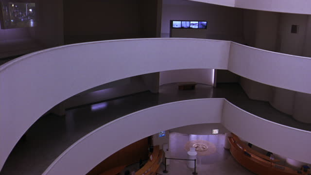 pan left to right of floors or levels of guggenheim museum. atrium. digital video art exhibit on walls. frank lloyd wright architecture. insignia on floor near reception area, information desks. - left atrium stock videos & royalty-free footage