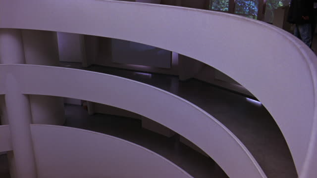 pan left to right and down of floors or levels of guggenheim museum. digital video art exhibit on walls. atrium or lobby. frank lloyd wright architecture. insignia on floor near reception area, information desks. ramp on ground level. retractable belt sta - left atrium stock videos & royalty-free footage