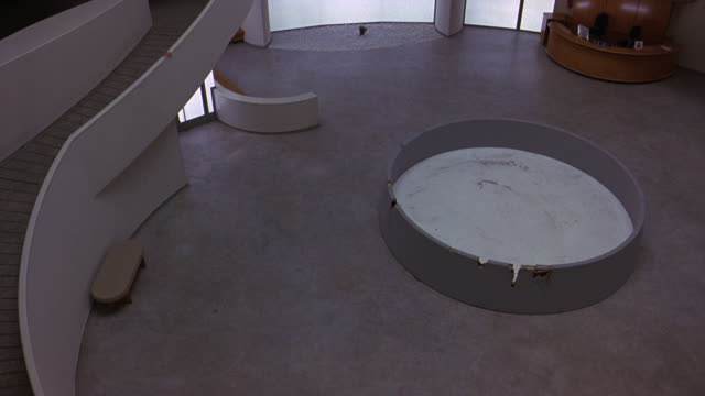 pan left to right of ground floor of guggenheim museum. atrium or lobby. frank lloyd wright architecture. reception area. retractable belt stanchions. circular art piece in center. - left atrium stock videos & royalty-free footage